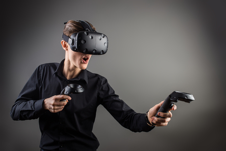 technology, gaming, entertainment and people concept - happy young man with virtual reality headset or 3d glasses with controller gamepad playing racing video game