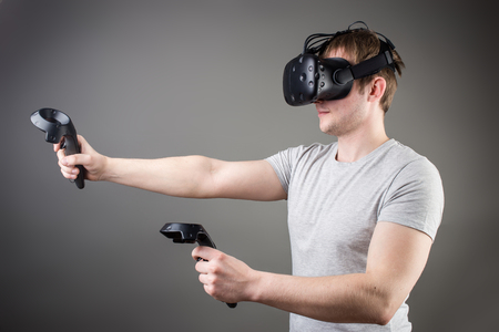 mediated: technology, gaming, entertainment and people concept - happy young man with virtual reality headset or 3d glasses with controller gamepad playing racing video game at home