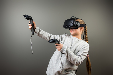 Child with virtual reality headset and joystick playing video games Banco de Imagens