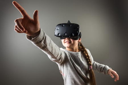girl wearing virtual reality goggles standing on grey background. VR glasses. 360 degrees. Virtual reality headset. VR game. Wearing virtual reality goggles. Smartphone with VR. Virtual reality video.
