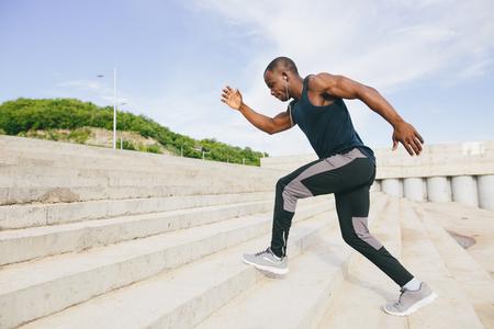 建物の外階段を実行しているオスの運動選手の側面図
