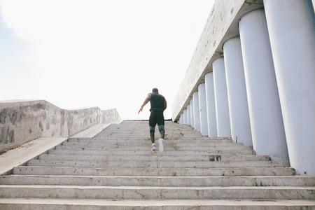 athletic wear: African black sportsman running upwards with energy on the stadium bleachers