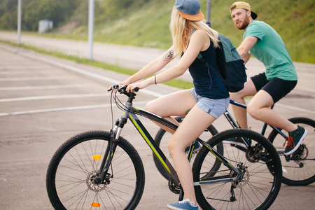 Side view of a young couple on cycle ride in countryside