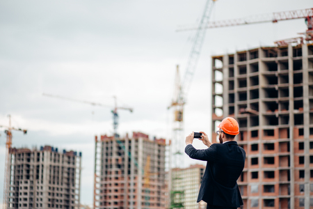 old photo: Construction engineer with the smartphone. Pictures of the construction site Stock Photo