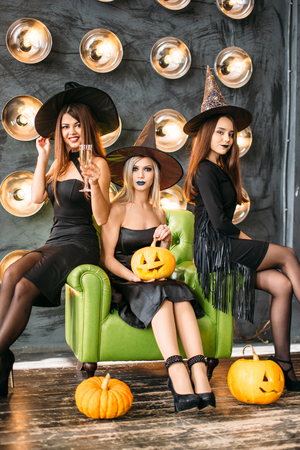 three emotional young women in halloween costumes having fun on party Stock Photo
