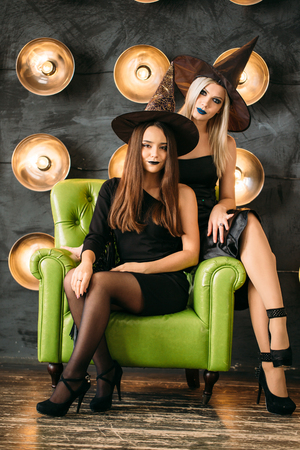 Two happy young women in black witch halloween costumes on party sitting on chair over white background