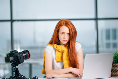sad redhead girl vlogger sitting at table with laptop and looking at camera.