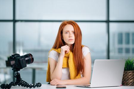 sad redhead girl vlogger sitting at table with laptop and looking at camera.