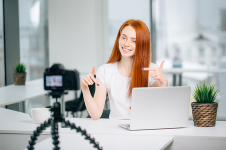female blogger with laptop and book on camera screen and show subscribe gesture Stock Photo