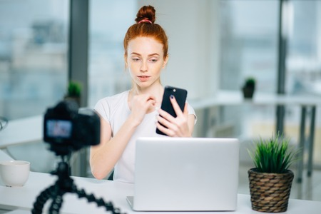 Young female redhead blogger with laptop recording video at home and take selfie Stock Photo