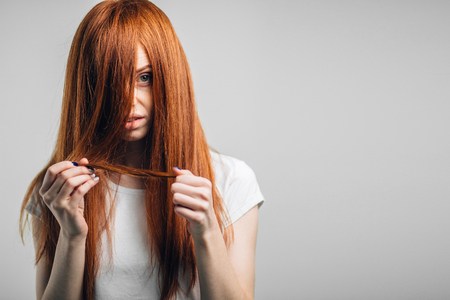 Sad redhead girl holding her damaged hair looking at camera. Stock Photo