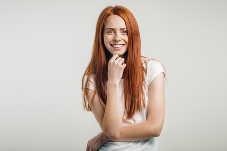 freckled girl with hair knot having fun indoors and looking at camera with smile