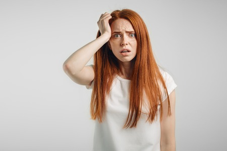 redhead girl on white background with strong expression of fear, round eyes