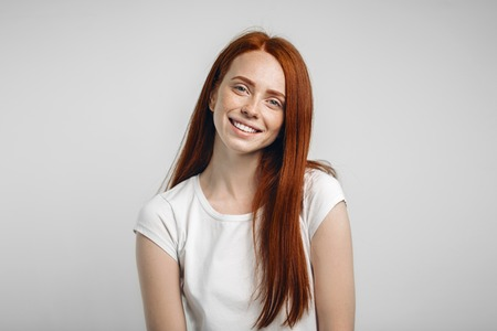Headshot Portrait of happy ginger girl with freckles smiling looking at camera