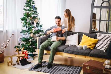 Young couple with gifts in front of Christmas tree Stock Photo