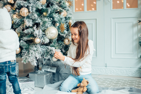 Two Young Girls havung fun In Front Of Christmas Tree