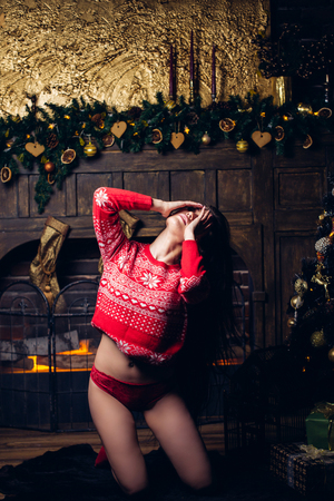 Woman in Christmas Sweater. Girl with Makeup and Dark Curly Hairstyle at Home