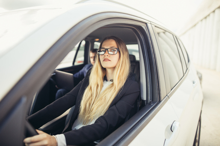 Beautiful happy business woman driving her car