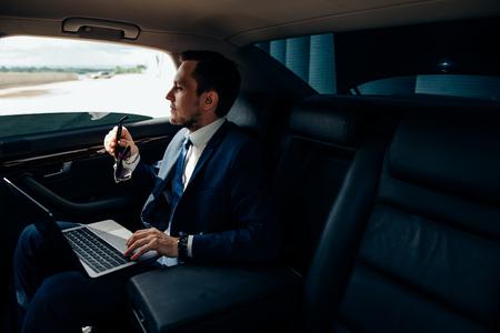Empresario serio en un auto con laptop