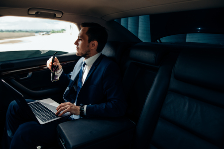 Serious businessman in a car with laptop