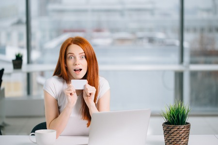 Shocking redhead woman with laptop and credit card Stock Photo