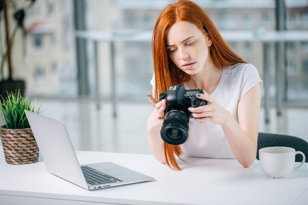 redhead woman looking at camera while working on laptop