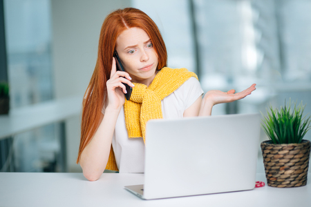 Furious woman wearing suit working on line using smart phone in a desk at office
