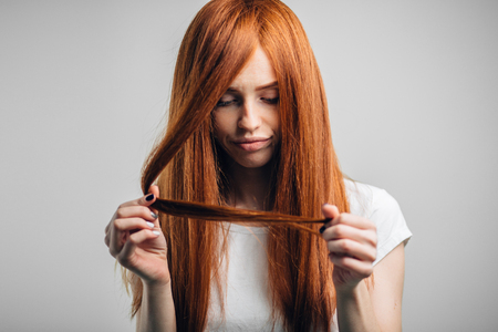 Sad redhead girl looking at her damaged hair
