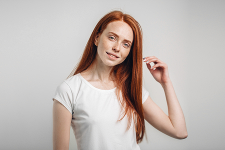 girl smiling with closed eyes touching her red hair over white background Stock Photo