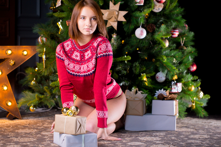 Beautiful Sexy Woman in Red Christmas Sweater. Winter Woman with Christmas Gift