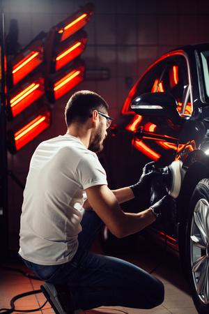 Car detailing - man with orbital polisher in auto repair shop. Selective focus. 写真素材