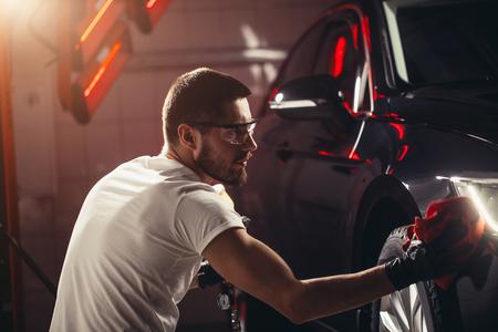 coche de detallando - el hombre sostiene el microscopio en la mano y el corrector del coche