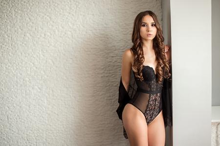 Sexy woman in black lingerie posing indoor