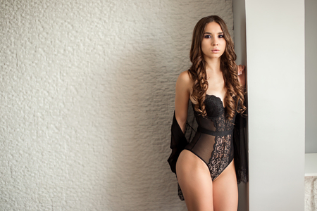 Sexy woman in black lingerie posing indoor