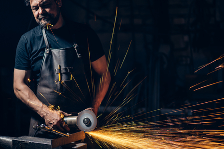 Electric Grinders metal with many sharp sparks, with confined space Stock Photo