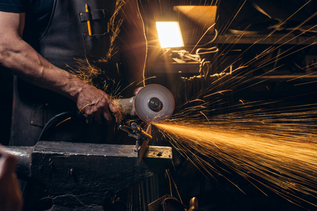 man Using Angle Grinder in Factory and throwing sparks Stock Photo