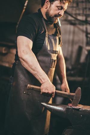 Senior blacksmith forging molten metal on the anvil in smithy. Imagens - 91105053