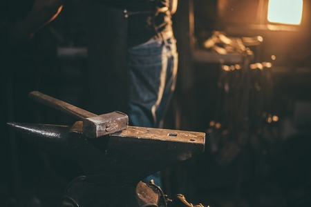 Blacksmith working on metal on anvil at forge