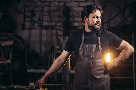 blacksmith portrait with beard in workshop 스톡 콘텐츠