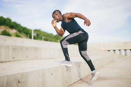 African black sportsman running upwards with energy on the stadium bleachers