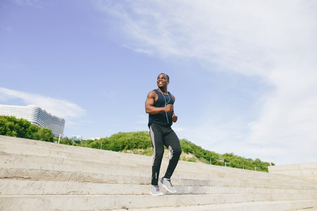 African young man athlete steps up with energy in bleachers
