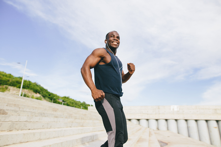 man african running up flight of stairs, training outdoor while jogging up steps