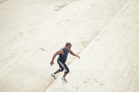 side view of a male athlete running up staircase outside building Stock Photo