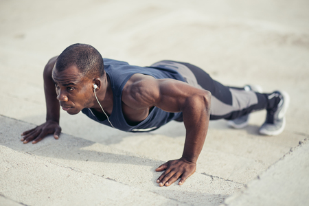 man doing push-ups. Fitness model doing outdoor workout