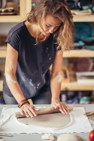 female potter molding clay with rolling pin in pottery workshop