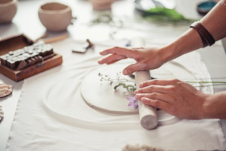 Artist rolls raw clay using big grey rolling pin on table covered in workshop 스톡 콘텐츠