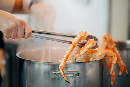 blue crabs in a steel pan with boiling water