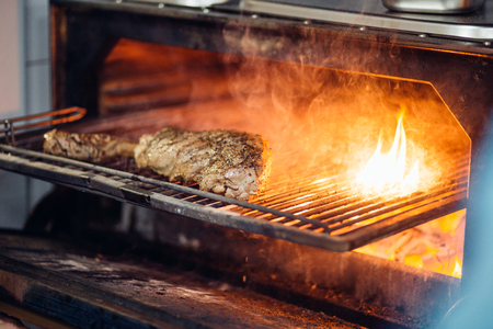 steaks cooking over flaming grill on restoraunt kitchen