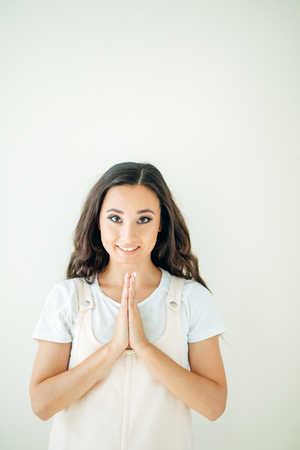 Woman praying hands together, namaste, yoga. Beautiful smiling brunette