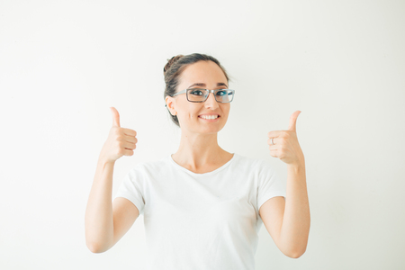 woman giving a thumbs up gesture of approval and success with a beaming smile